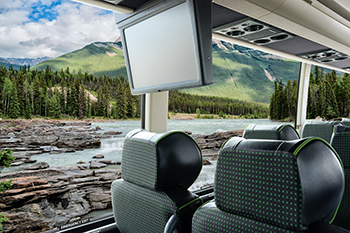 Charter bus interior showcasing leather seats dvd screen and outside window with river and mountain landscapes
